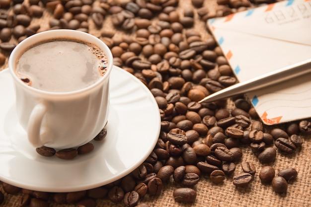 Xícara de café branca; uma carta e uma caneta na mesa
