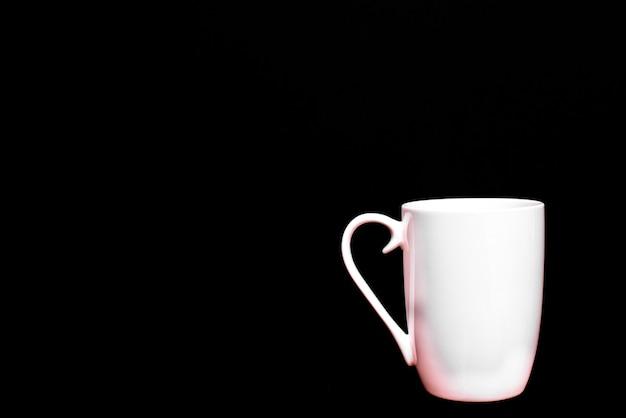 Xícara de café branca, vazia e em branco, isolada em preto com espaço de cópia.