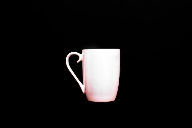 Xícara de café branca, vazia e em branco, isolada em um fundo preto com espaço de cópia.