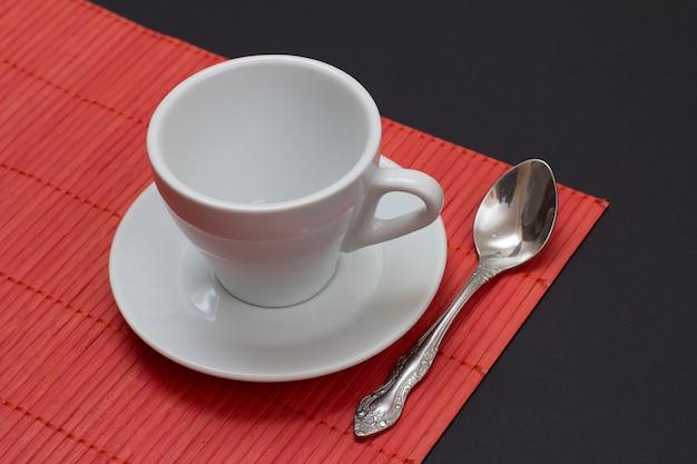 Xícara de café branca vazia, pires e colher de aço inoxidável no guardanapo de bambu vermelho com fundo preto. vista do topo.