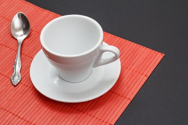 Xícara de café branca vazia, pires e colher de aço no guardanapo de bambu vermelho com fundo preto. vista do topo.