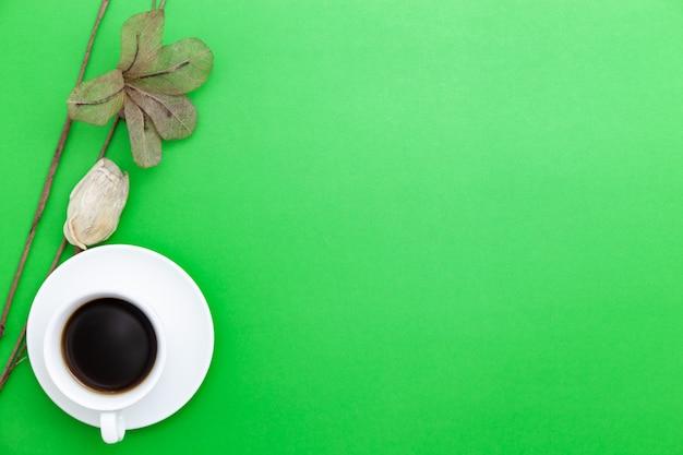 Xícara de café branco com flor de papel em fundo de papel verde.