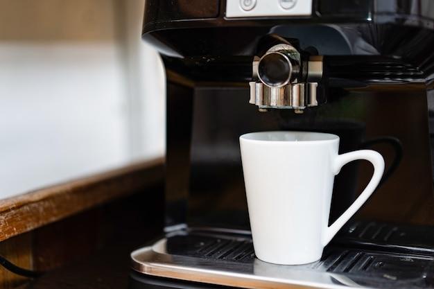 Xícara de café branco em espera na máquina de café profissional pronta para fazer café quente fresco.