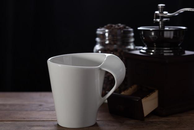 Xícara de café branco, moedor de café e feijão torrado na mesa de madeira com fundo escuro