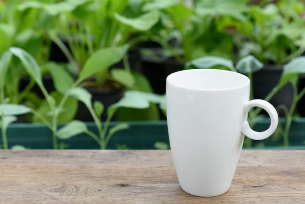 Xícara de café branco na prancha de madeira na horta