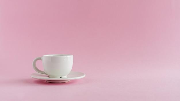 Xícara de café branco sobre fundo rosa