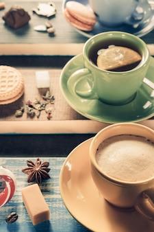 Xícara de café, cacau e chá em fundo de madeira