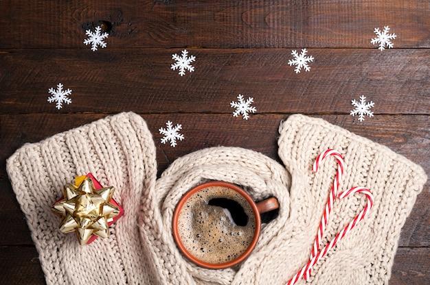 Xícara de café, cachecol de tricô, caixa de presente presente, flocos de neve e bastões de doces no fundo de natal