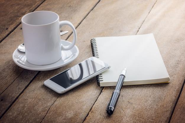 Xícara de café, caderno, caneta e telefone inteligente