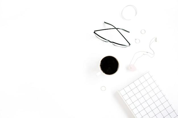 Xícara de café, caderno, óculos e acessórios femininos na superfície branca