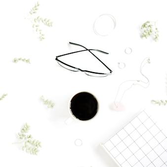 Xícara de café, caderno, óculos, ramos verdes e acessórios femininos na superfície branca