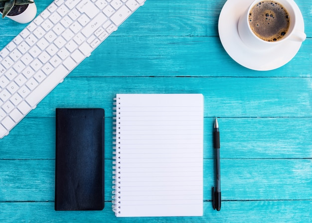 Xícara de café, cadernos, caneta na mesa de madeira turquesa