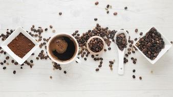 Xícara de café; café em pó e grãos de café dispostos em uma fileira na mesa