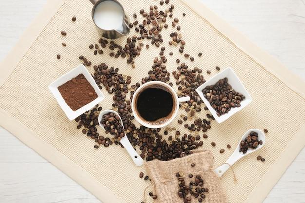 Xícara de café; café em pó; grãos de café e pequeno saco no placemat