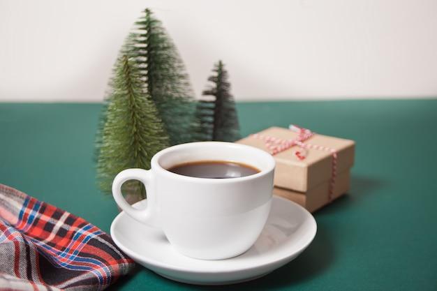 Xícara de café, caixa de presente de natal e três brinquedos pequenos de árvore de natal em cima da mesa verde.