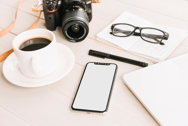 Xícara de café; câmera; celular; caneta; óculos no caderno sobre a mesa de madeira