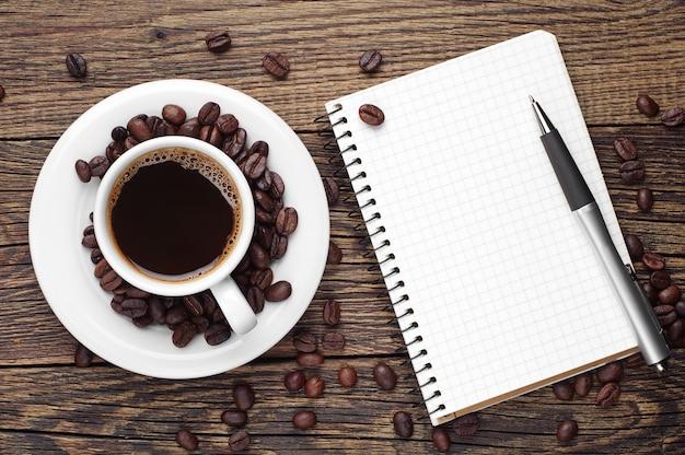 Xícara de café, caneta e bloco de notas aberto na mesa