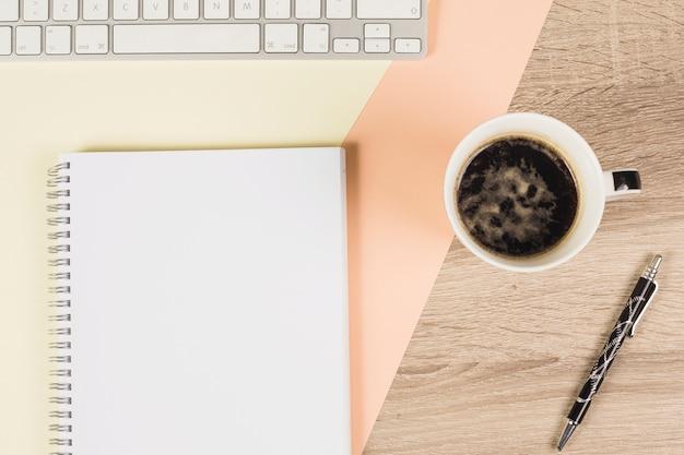 Xícara de café; caneta; teclado; e caderno espiral no fundo colorido e de madeira