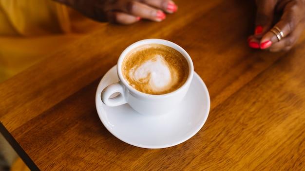 Xícara de café cappuccino com arte de latte de forma de coração na superfície de madeira