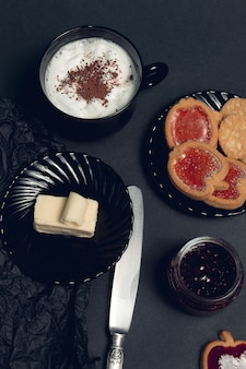 Xícara de café, cappuccino com biscoitos de chocolate e biscoitos na mesa preta. hora do intervalo da tarde. café da manhã. vista do topo.