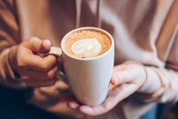Xícara de café cappuccino com coração de espuma nas mãos femininas no café, close-up