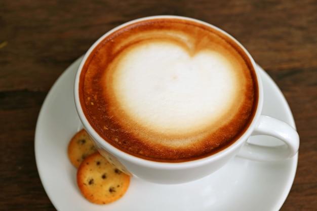 Xícara de café cappuccino com espuma de leite fofo branco em cima da mesa de madeira