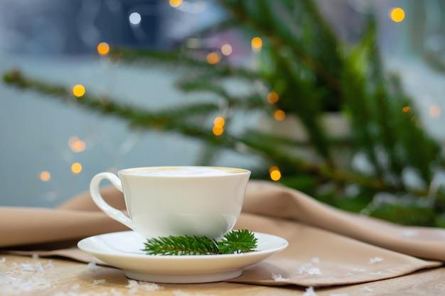 Xícara de café cappucino delicioso com vaga-lumes e ramos de abeto