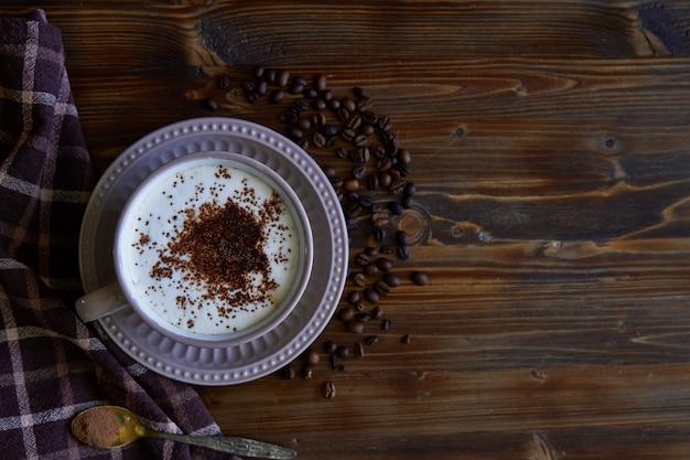 Xícara de café capuccino com canela e grãos de café na copyspace de madeira