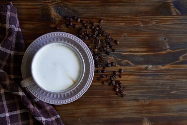 Xícara de café capuccino com grãos de café na madeira