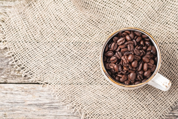 Xícara de café cheia de grãos de café com espaço de cópia. vista do topo.