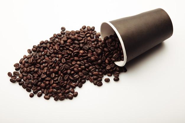 Xícara de café cheia de grãos de café.