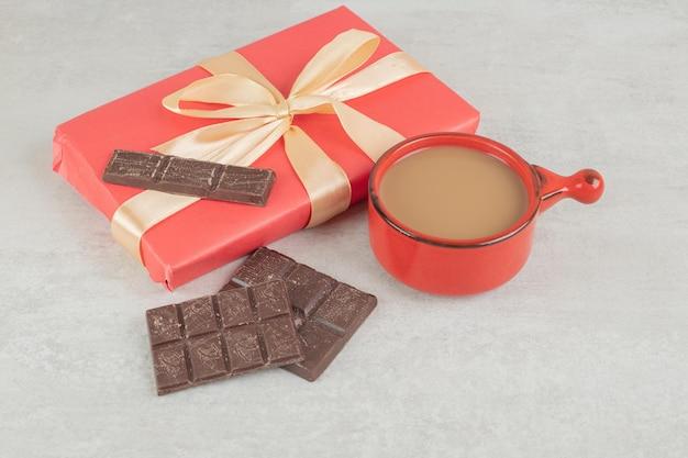 Xícara de café, chocolate e caixa de presente em superfície de mármore.