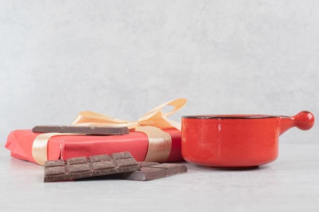 Xícara de café, chocolate e caixa de presente em superfície de mármore