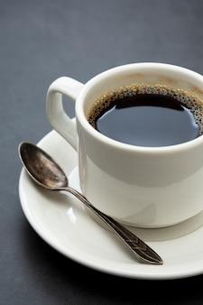 Xícara de café close-up. xícara de café branca vista superior colher e prato em fundo escuro