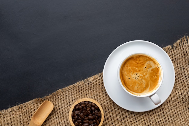 Xícara de café, colher de pau e grãos de café em uma tigela
