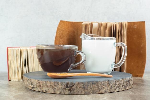 Xícara de café, colher e leite no pedaço de madeira.