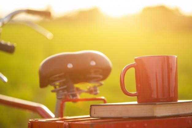 Xícara de café, colocar na bicicleta clássica estilo vermelho do japão à vista do campo de arroz verde