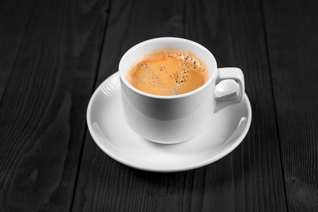 Xícara de café com açúcar mascavo em uma mesa de madeira.
