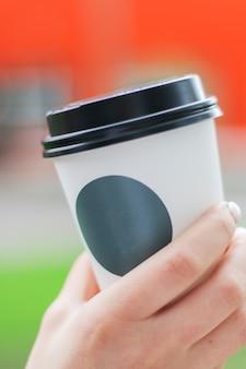 Xícara de café com adesivo para logotipo na mão da mulher com dof raso