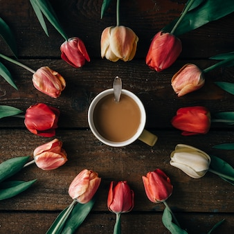 Xícara de café com arranjo criativo de tulipas na parede de madeira escura. postura plana.