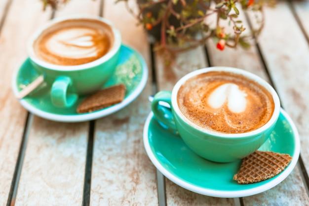 Xícara de café com arte de latte de forma de coração na mesa de madeira