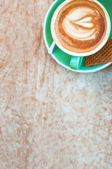 Xícara de café com arte de latte de forma de coração no pano de fundo texturizado de madeira