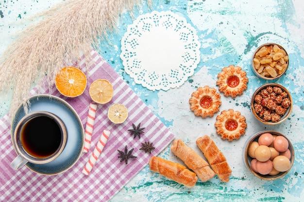 Xícara de café com bagels e biscoitos no bolo de fundo azul claro com vista de cima