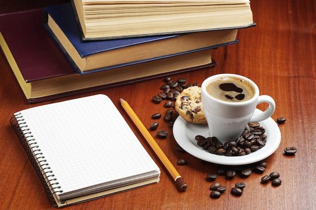 Xícara de café com biscoitos, bloco de notas e livros na mesa