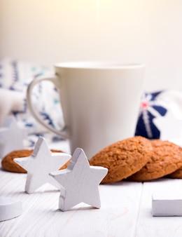Xícara de café com biscoitos de aveia e enfeites de natal