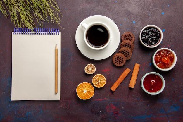 Xícara de café com biscoitos de chocolate e geleias de frutas no fundo escuro.