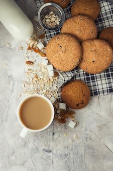 Xícara de café com biscoitos de leite e aveia em uma superfície de pedra. copo cerâmico branco, aveia, passas, cubos de açúcar, garrafa de leite. cena do café da manhã