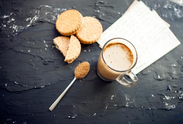 Xícara de café com biscoitos e açúcar marrom xícara de café com leite fresco servida com chocolate
