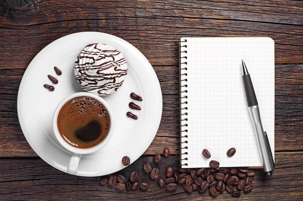 Xícara de café com biscoitos e caderno aberto na velha mesa de madeira