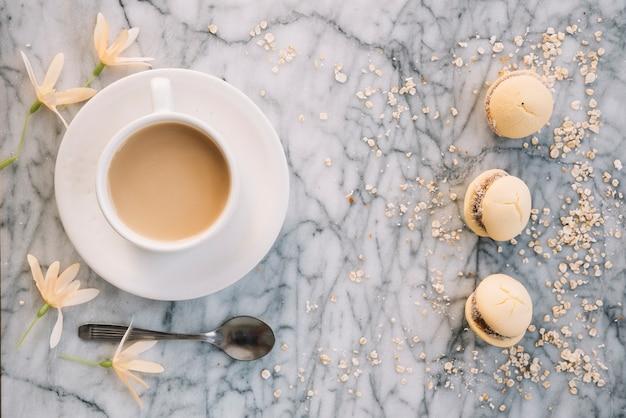 Xícara de café com biscoitos e flores na mesa
